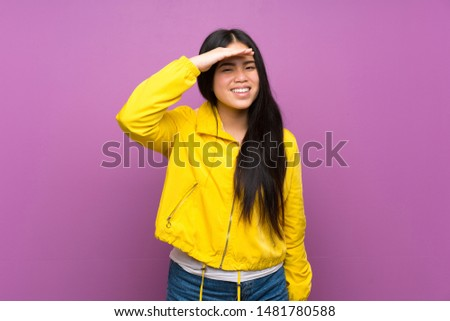 Young teenager Asian girl over isolated purple background looking far away with hand to look something