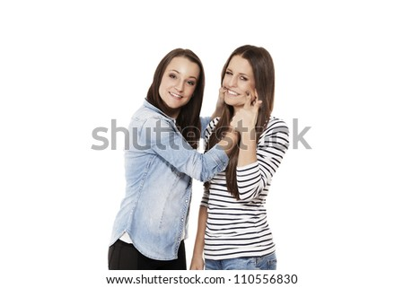young teenager forcing her friend to laugh on white background
