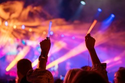 Young teenager girl fan raised up two hands with colored glowing sticks supporting favorite popular band on the night concert. Colorful crowdy background entertainment with light and laser show.