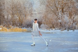 Young teenager girl in white dress with  ice skates racing frozen lake or river among frosted trees. Outdoor winter sports concept