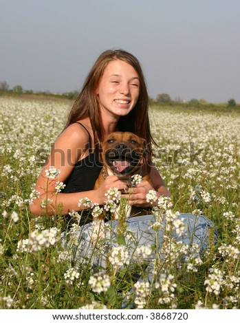 young teenager in a field with her dog