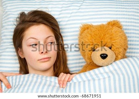 Young Teenager in Bed Looking Askance at Her Teddy Bear