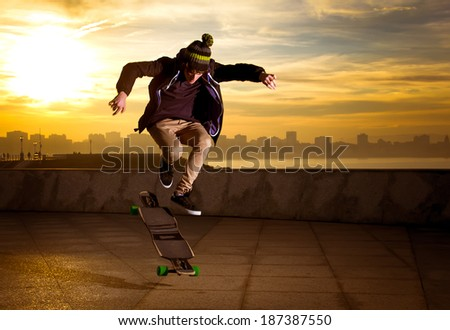 young teenager jumping with a longboard