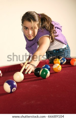 Young teenager playing pool on a red table