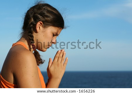 Young teenager praying by the sea