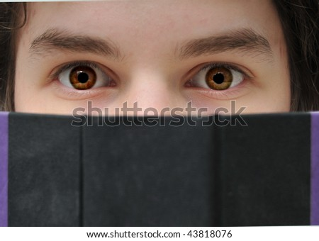 Young teenager reading a book closeup with brown eyes.
