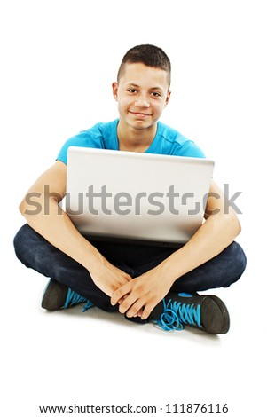 Young teenager with laptop sitting on the floor.  Isolated on a white background.