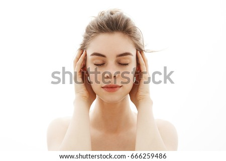 Young tender nude girl with bun posing over white background. Closed eyes. #666259486