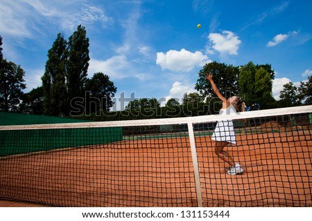 Young tennis player hitting a ball over the net on the court