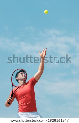 Young tennis player with racket throws the ball prepares to serve at beginning of game or match. Cute male tennis player athlete in action. Competitive sport. Vertical banner Copy space
