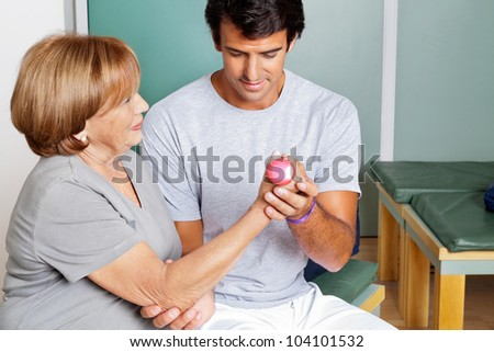 Young therapist giving muscle training for elbow joint at clinic