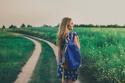 young thin blonde woman stands in dress and backpack on her shoulder in middle of green field On walking path in summer at sunset