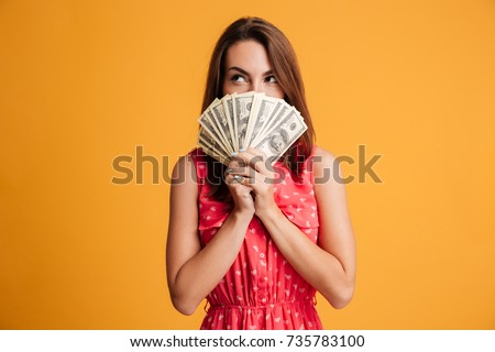 Young thinking pretty woman in red dress hiding behind bunch of money banknotes, looking upward, isolated on yellow background
