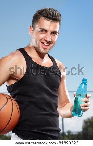 Young thirsty man drinking water on sports field