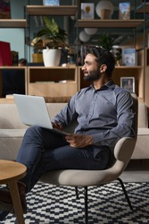 Young thoughtful bearded smart indian professional business man executive looking away sitting on chair in modern office lobby using laptop, thinking of new ideas, planning project, working online.