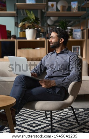 Young thoughtful bearded smart indian professional business man executive looking away sitting on chair in modern office lobby using laptop, thinking of new ideas, planning project, working online. Foto d'archivio ©