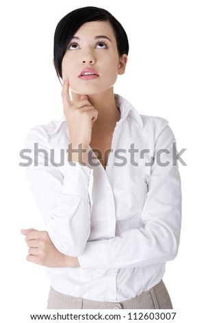 Young thoughtful businesswoman looking up