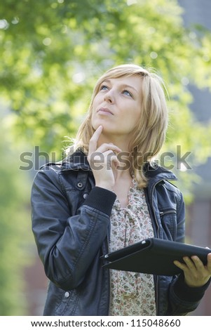 Young thoughtful Caucasian woman with digital tablet looking up outdoors