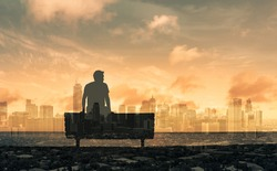 Young thoughtful man sitting looking a the city skyline dreaming and thinking.  Double exposure.