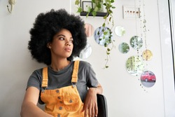 Young thoughtful pensive stylish African American gen z female hipster woman with afro hair looking through window thinking reflecting sitting lost in thoughts at home, in modern cafe alone indoors.
