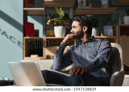 Young thoughtful smart indian professional business man executive looking away relaxing sitting on chair in modern office lobby with laptop, thinking of new ideas, dreaming of success, planning.