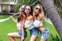 Young three happy beautiful girls best friends having fun at summer time, posing at park near hammock, sending air kiss smiling and fun, joy, vacation time.