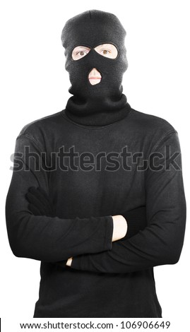 Young thug turned criminal posing with his arms folded wearing a black outfit with hooded mask to conceal his identity, isolated on a white studio background