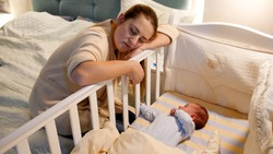 Young tired and exhausted mother fallen asleep while rocking crib of her newborn baby at night. Concept of sleepless nights and parent depression after childbirth.