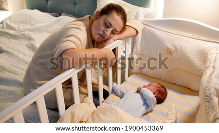 Young tired and exhausted mother fallen asleep while rocking crib of her newborn baby at night. Concept of sleepless nights and parent depression after childbirth. Foto stock ©