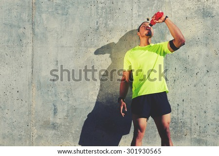 Young tired athlete refreshing with energy drink while standing against cement wall background with copy space area for your text message or content, male runner resting after exercise outdoors