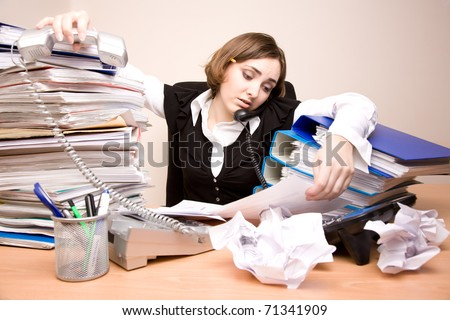 Young tired businesswoman with tons of documents calling phone