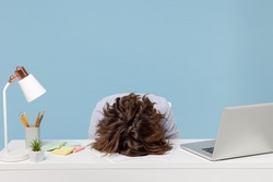 Young tired exhausted frustrated secretary employee business woman wearing casual shirt sit work sleep laid her head down on white office desk with pc laptop isolated on pastel blue background studio