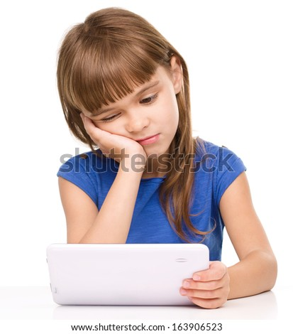 Young tired girl is using tablet while sitting at table supporting her head with hand, isolated over white