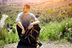 Young tired hiker with backpack sitting on the mountain top while resting after active walk, active traveler man hiking in beautiful nature in sunny day, male tourist taking break after long hike way