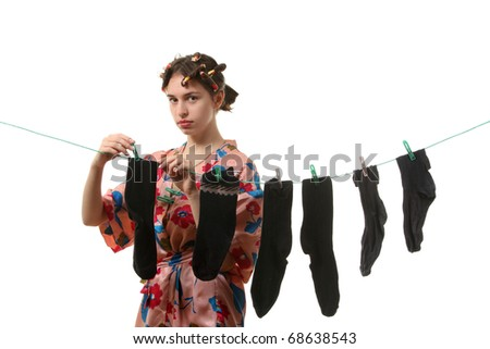 Young tired housewife hangs up socks on  the clothesline