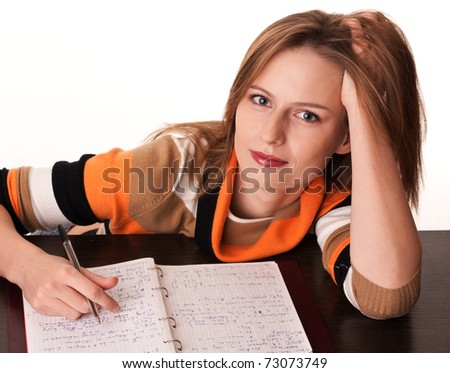 Young tired student on the desk with her notes dreaming looking at camera