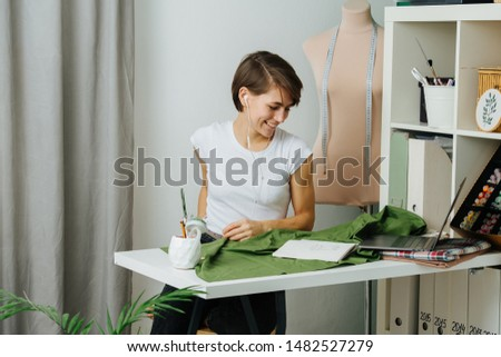Young tired tailor woman sitting at her workplace, behind the desk listening to earbuds, enjoying music during coffee break at office. She has short brown hair, casually dressed.