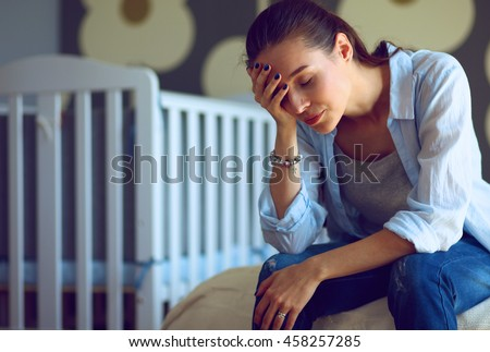 Young tired woman sitting on the bed near children\'s cot.