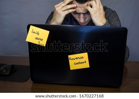 young tired worker thinks in front of a laptop in a dark room