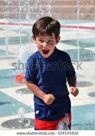 Young toddler boy playing in the water fountain