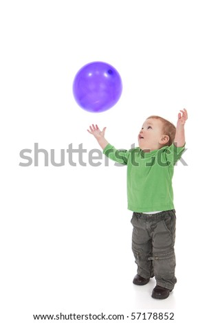 Young toddler boy throwing and catching purple balloon. Isolated on white