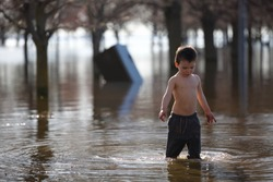 Young toddler plays in water of flooded park after heavy rain storm