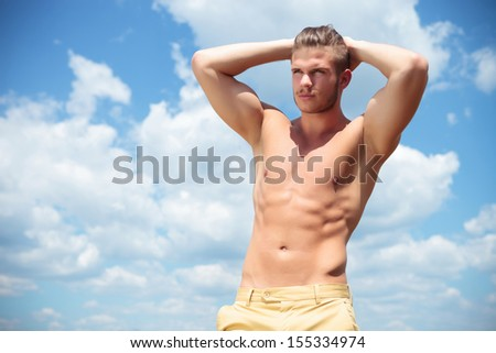 young topless man posing outdoor with his hands at the back of his head while looking away