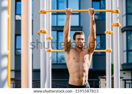 Young topless muscular athlete hanging on sports bar while pulling up on sportsground during workout.Naked torso man looking away, relaxing after exercises. Sport, lifestyle and people concept.