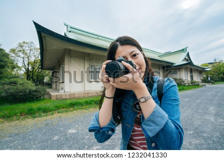 young tourism lens man taking picture by the camera smiling. joyful attractive professional photographer using digicam shot. beautiful girl love photography travel outdoor in summer.