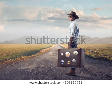 Young tourist carrying a suitcase on a country road