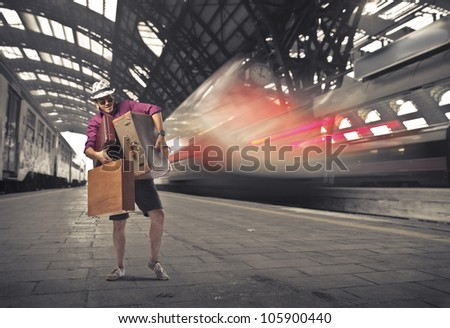Young tourist carrying many suitcases on the platform of a train station