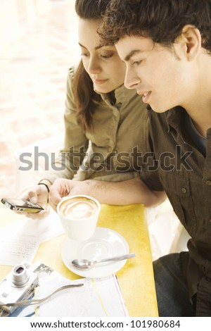 Young tourist couple drinking coffee and using a cell phone while on vacations.