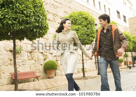 Young tourist couple holding hands and running through a town's square.