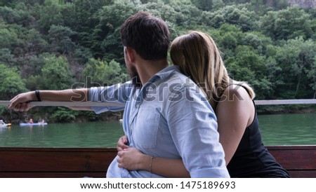 Young tourist couple hugging in a small wood boat in an activity in the river. Girl hug a boy with black beard from the backside enjoying an excursion with forest in a canyon. #1475189693
